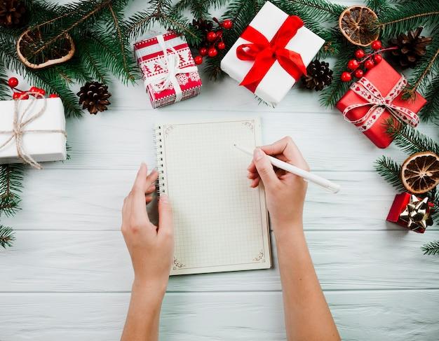 Handen met notitieboekje dichtbij kerstmistakje Gratis Foto