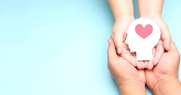 Handen met papier hersenen en hart. Premium Foto