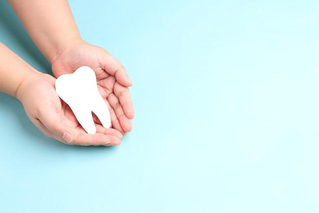 Handen met papier tanden op blauw. Premium Foto