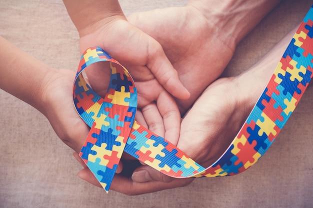 Handen met puzzel lint voor autisme bewustzijn Premium Foto