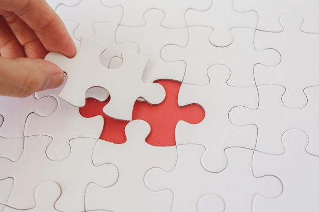 Handen met puzzelstukken, bedrijfsstrategieplanning Premium Foto