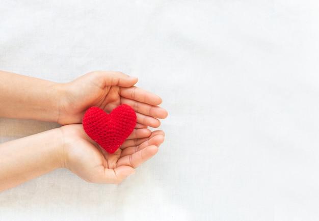 Handen met rood hart, concept van liefde, hoop, orgaandonatie, verzekering, wereldhartdag. Premium Foto