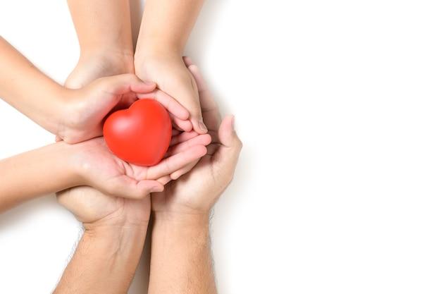 Handen met rood hart, hartgezondheid, schenking, gelukkige vrijwilligers liefdadigheid, mvo sociale verantwoordelijkheid, wereldhartdag, wereldgezondheidsdag, wereld geestelijke gezondheidsdag, pleeggezin concept Premium Foto
