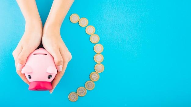 Handen met roze spaarvarken Gratis Foto