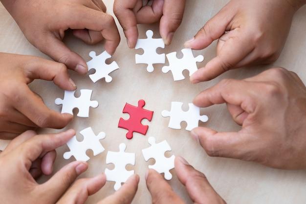 Handen met stuk van de lege puzzel met houten tafel achtergrond. Premium Foto