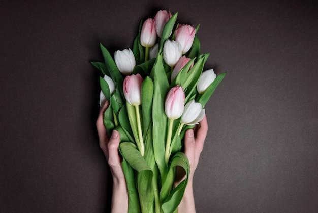 Handen met tulpen. het concept van bloemen leggen aan gevallen helden Premium Foto