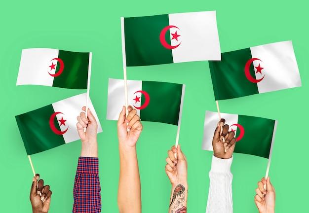 Handen met vlaggen van algerije zwaaien Gratis Foto
