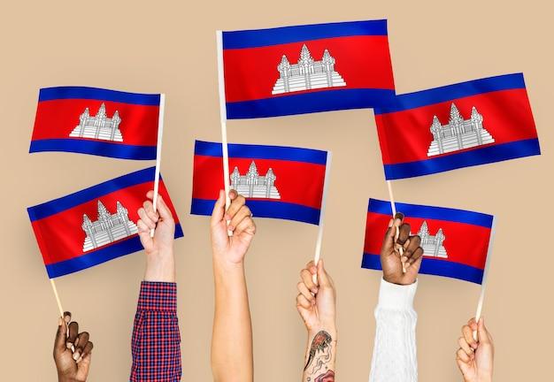 Handen met vlaggen van cambodja zwaaien Gratis Foto