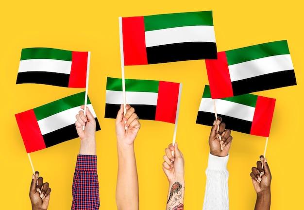 Handen met vlaggen van de verenigde arabische emiraten zwaaien Gratis Foto