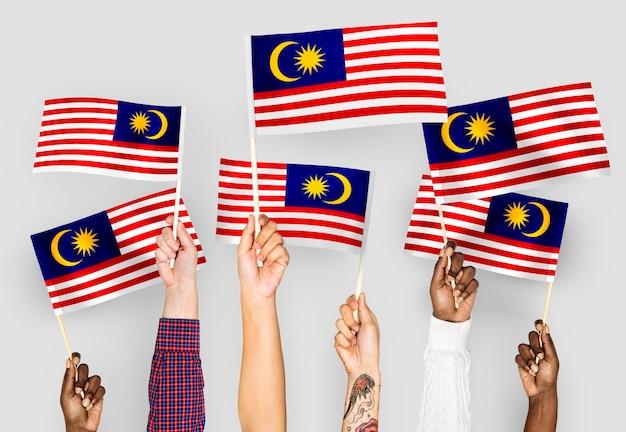 Handen met vlaggen van maleisië zwaaien Gratis Foto