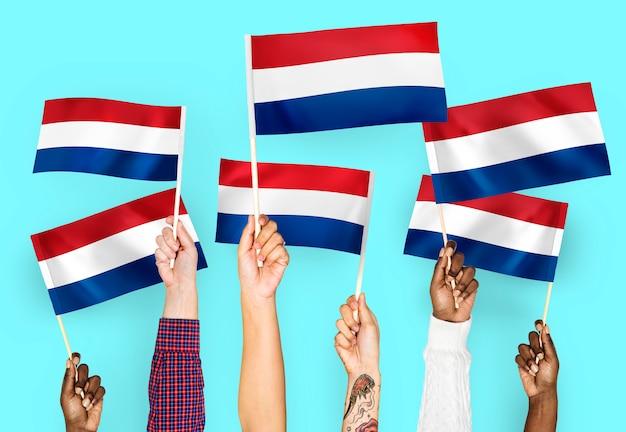 Handen met vlaggen van nederland zwaaien Gratis Foto