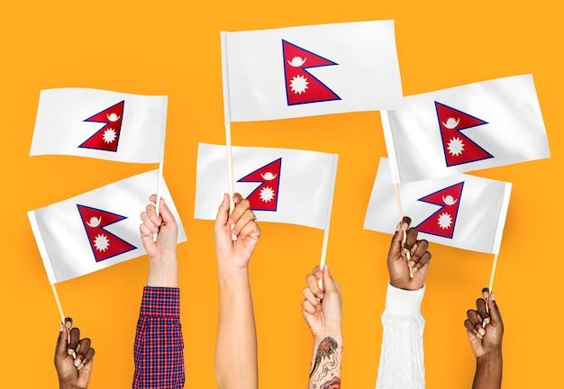 Handen met vlaggen van nepal zwaaien Gratis Foto