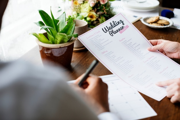 Handen met wedding planner checklist informatie voorbereiding Gratis Foto