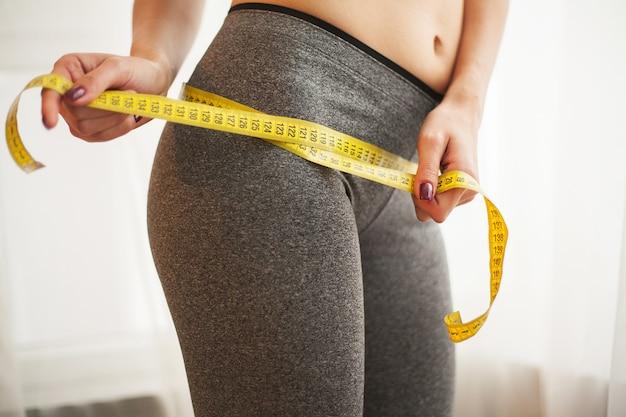 Handen meten taille met een tape. slanke en gezonde vrouw bij haar thuis Premium Foto