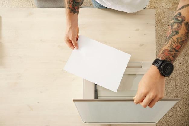 Handen openen een scannerlade en leggen een vel papier om een document te scannen op multifunctioneel elektronisch apparaat thuis, geïsoleerd op witte houten tafel, bovenaanzicht Gratis Foto