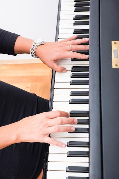 Handen os een klassieke musicusvrouw die op piano speelt. Premium Foto