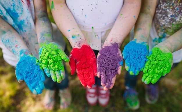Handen / palmen van jonge mensen bedekt met paarse, gele, rode, blauwe holi festival kleuren geïsoleerd Premium Foto