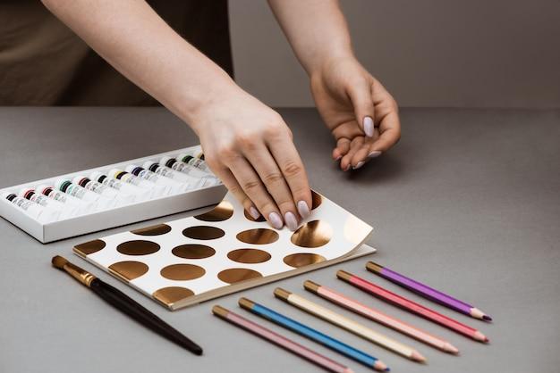 Handen schetsboek openen met olieverf en potloden op grijze tafel Gratis Foto