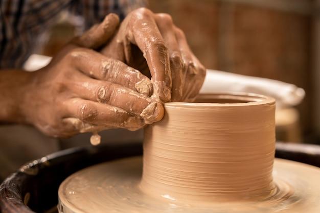 Handen van artisanale roterende werkstuk van aarden pot houden tijdens het werken door aardewerk wiel in zijn atelier Premium Foto