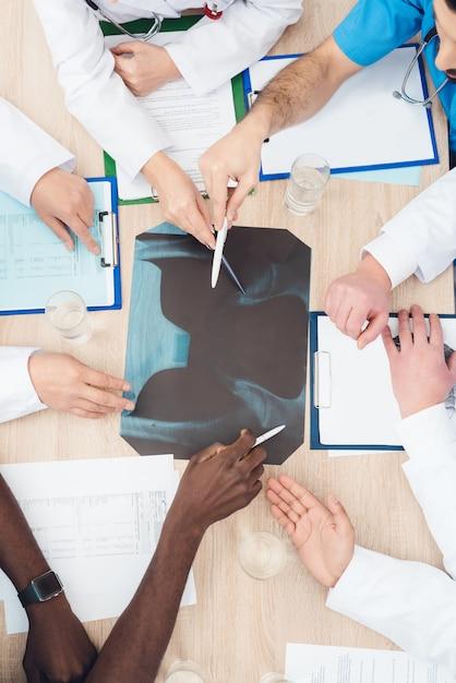 Handen van artsen van verschillende rassen worden op een röntgenfoto getoond. Premium Foto