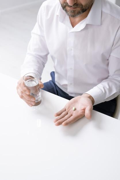 Handen van bebaarde zakenman met hoofdpijn pil en glas water houden over bureau in kantoor Premium Foto