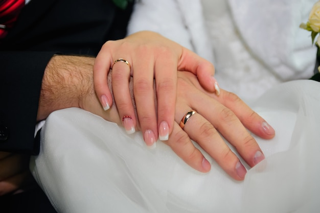 Handen van bruid en bruidegom met gouden trouwringen op witte jurk Premium Foto