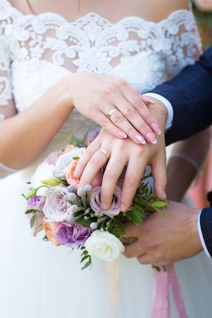 Handen van de bruid en bruidegom op het huwelijksboeket Premium Foto