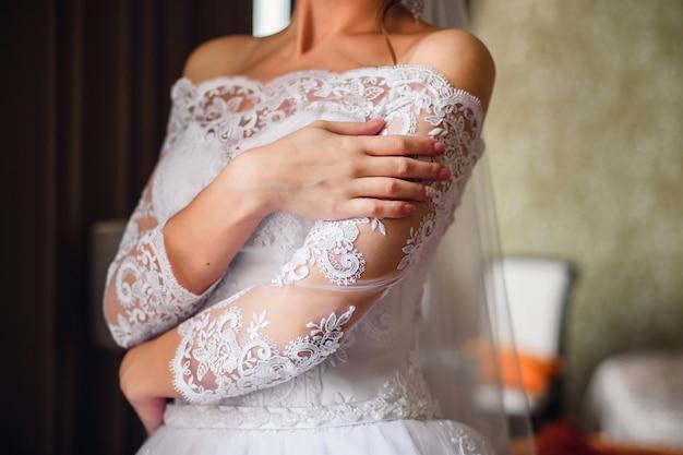 Handen van de bruid met een bruiloft manicure op nagels Premium Foto