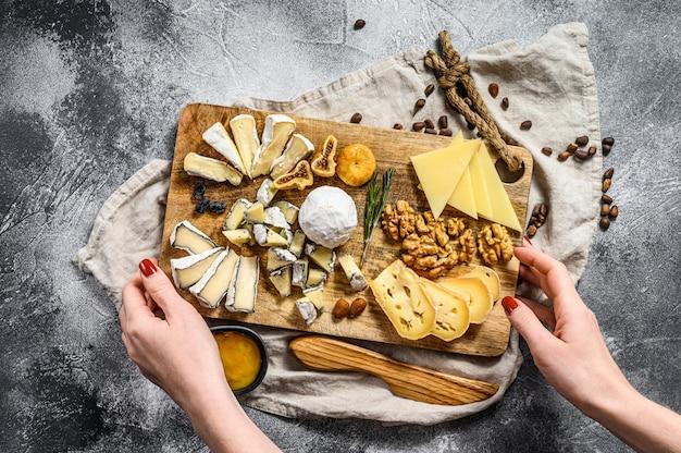 Handen van de chef-kok met een kaasschotel geserveerd met noten en vijgen. grijze achtergrond. bovenaanzicht Premium Foto