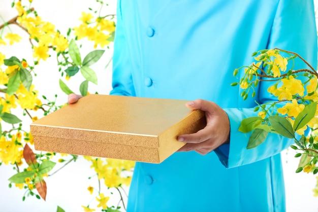 Handen van de onherkenbare man in traditionele jas poseren met bloeiende mimosa en vierkante doos Gratis Foto