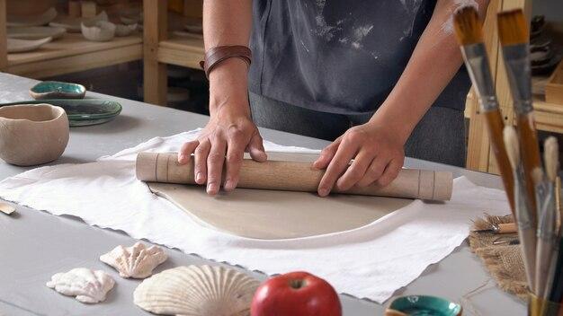 Handen van een close-up beeldhouwer die werkt in een werkplaats. Premium Foto