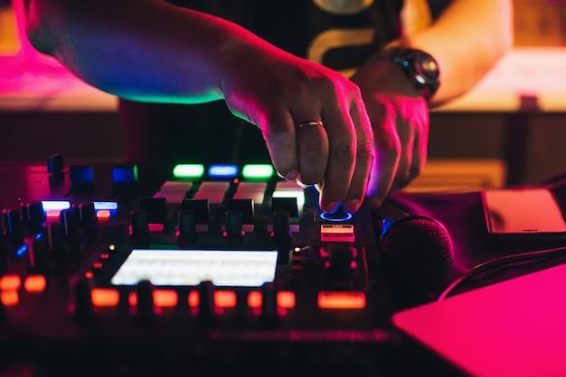 Handen van een dj die bij een professionele mixer in nachtclub speelt Premium Foto