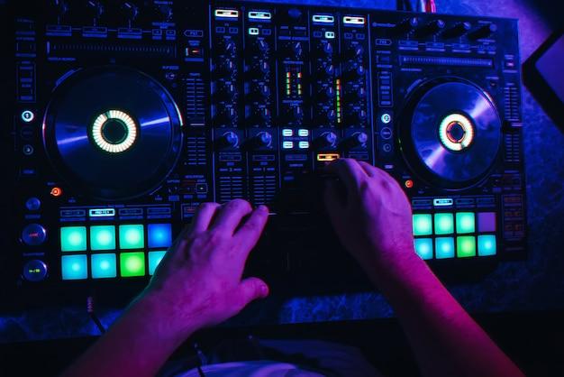 Handen van een dj in een cabine die op de mixer speelt Premium Foto