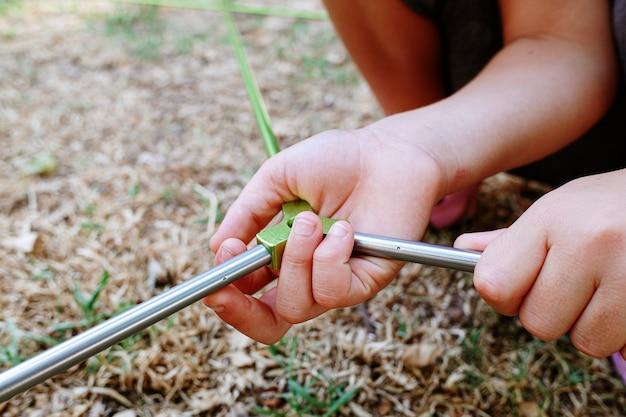 Handen van een kind dat zich bij de tralies van een tent aansluit om het op te zetten. Premium Foto