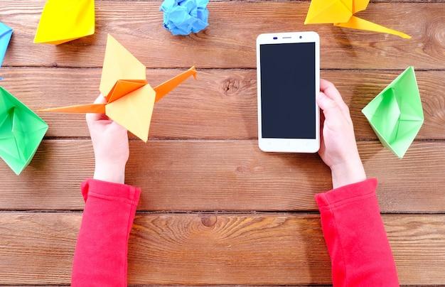 Handen van een kind met een telefoon en origami van gekleurd papier op een houten tafel Premium Foto