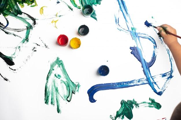 Handen van een kleine jongen die met waterverf op witboekblad schildert. Premium Foto
