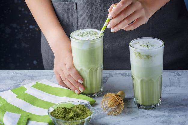 Handen van een meisje die een glas met groene latte houden. matcha groene thee en sojamelkdrank Premium Foto