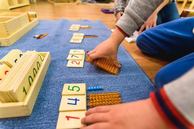 Handen van een student jongen met behulp van houten materiaal in een montessori-school. Premium Foto