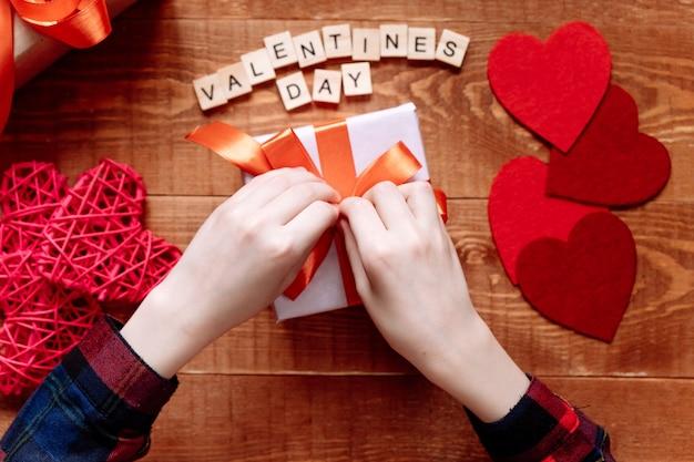 Handen van een tiener die een cadeau voorbereidt voor valentijnsdag op een houten achtergrond. harten en vakantiedecor op. Premium Foto