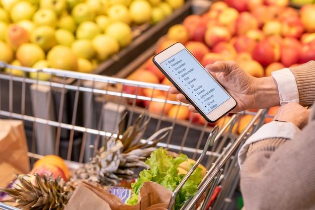 Handen van eigentijdse oude vrouw die door boodschappenlijst in smartphone over kar met verse groenten en fruit in supermarkt kijken Premium Foto