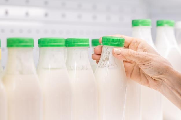 Handen van hedendaagse rijpe vrouwelijke consument die plastic fles kefir met groen deksel van plank op zuivelproductenvertoning neemt Premium Foto