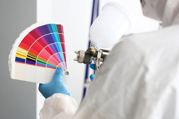 Handen van het airbrush van de werkmansholding en de kleurrijke toon van de fantail het plukken muur Premium Foto