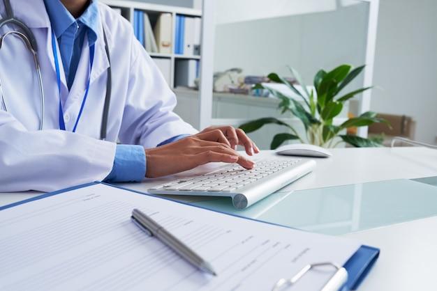 Handen van het onherkenbare vrouwelijke arts typen op toetsenbord in bureau Gratis Foto