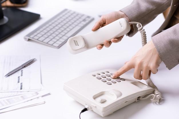 Handen van jonge kantoorsecretaris telefoonnummer kiezen en ontvanger vasthouden tijdens het bellen van een van de klanten per werkplek Premium Foto