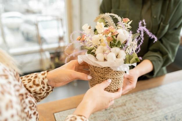 Handen van jonge vrouw die een klein mandje met bloemenboeket neemt tijdens een bezoek aan de bloemistwinkel om bloemen te kopen voor haar vriend of moeder Premium Foto