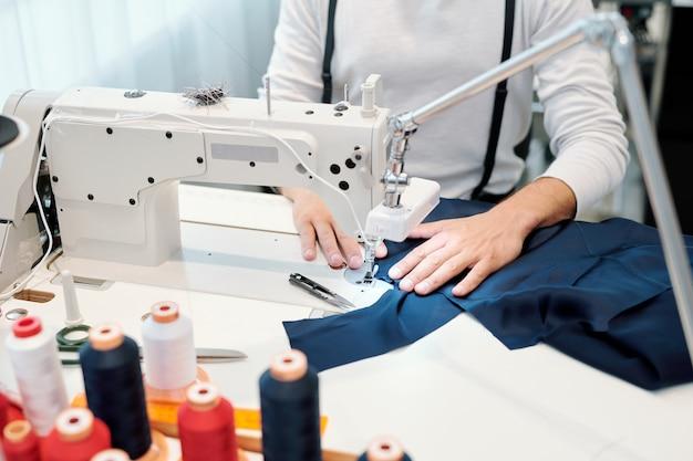 Handen van mannelijke kleermaker door naaimachine die donkerblauw stuk textiel vasthoudt tijdens het werken aan nieuw kledingstuk Premium Foto