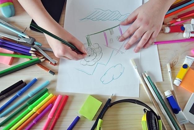 Handen van meisje die een afbeelding op je bureaublad schilderen Premium Foto