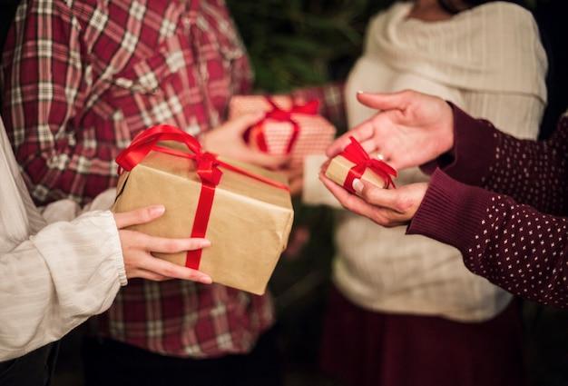 Handen van mensen die cadeaus ruilen voor kerstmis Gratis Foto