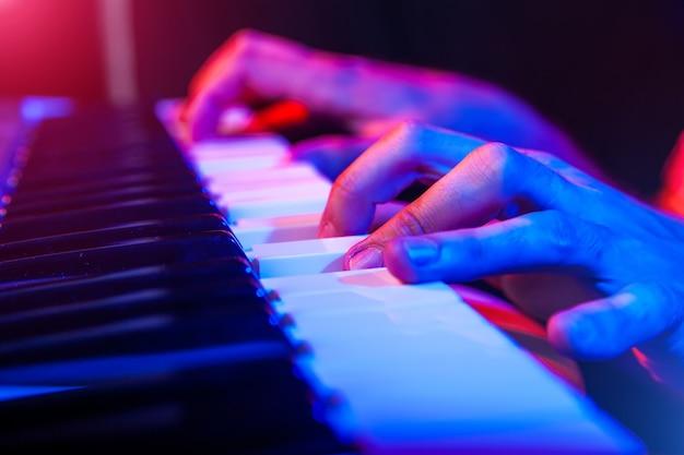 Handen van muzikant toetsenbord bespelen in concert met ondiepe scherptediepte Premium Foto