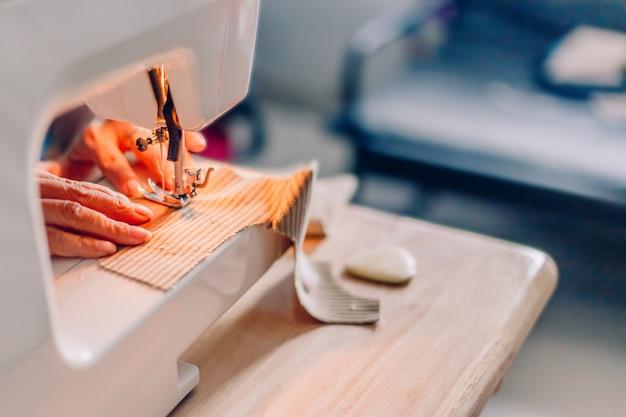 Handen van naaien proces. vrouwelijke handen die stof op machinehobby thuis stikken Premium Foto